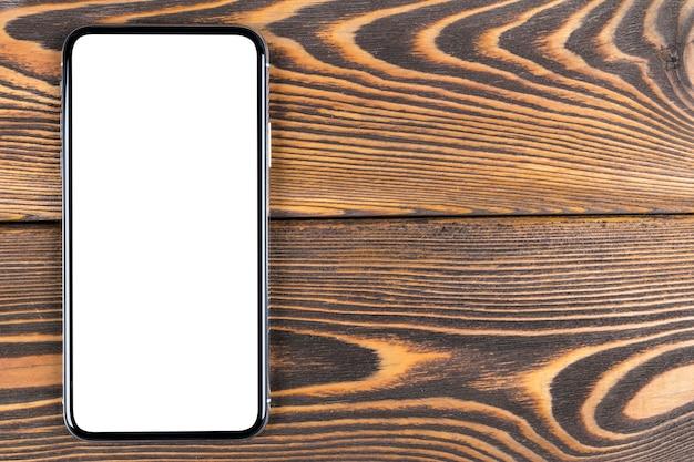 Smartphone avec écran blanc maquette. écran isolé de smartphone avec un tracé de détourage. écran blanc de téléphone portable avec espace copie sur le bureau. espace vide pour le texte. écran blanc isolé