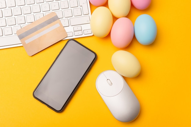 Smartphone avec écran blanc et oeufs de pâques avec carte de crédit