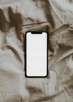 Smartphone écran blanc sur tissu texturé