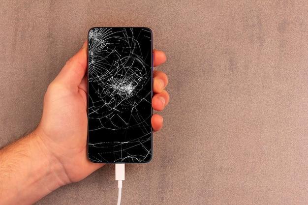 Smartphone avec écran cassé dans la main masculine sur fond gris-brun avec espace de copie
