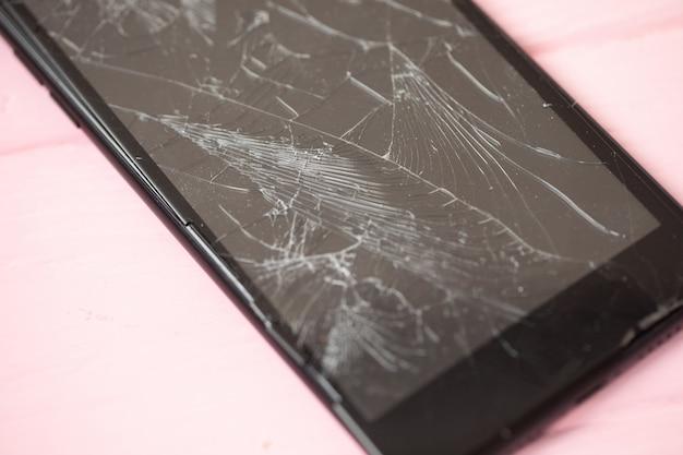 Smartphone avec écran cassé sur table rose