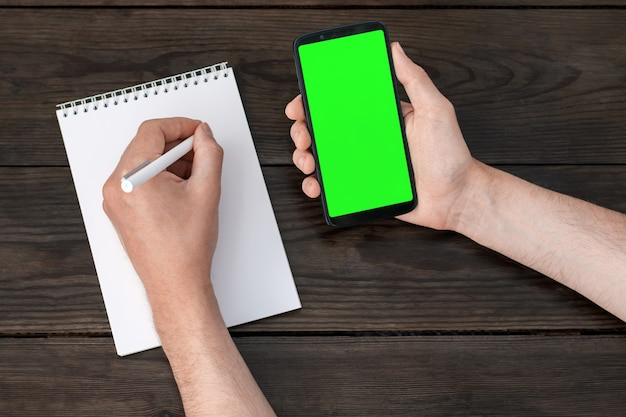Un smartphone avec un écran vert dans une main, un stylo dans les mains écrit dans un cahier dans l'autre main sur une table en bois.