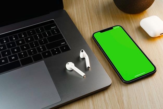 Smartphone avec un écran vert sur fond en bois avec un ordinateur. vue de dessus. clé chroma.