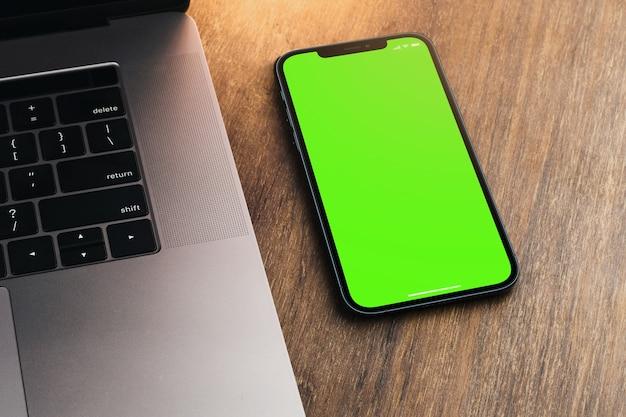 Smartphone à écran vert vierge sur fond en bois avec un ordinateur à côté. clé chroma.
