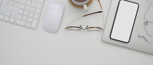 Smartphone à écran vide au-dessus du calendrier sur le bureau blanc avec des appareils informatiques, des lunettes, une tasse et un espace de copie