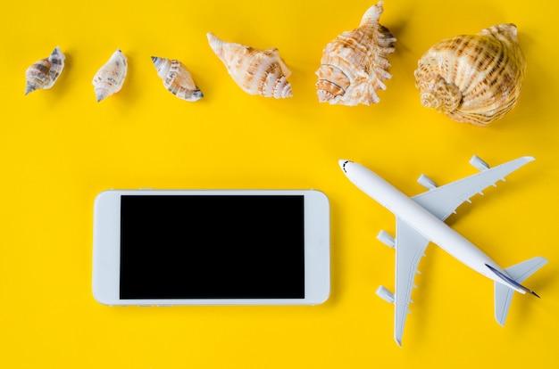 Smartphone à écran vide, avion décoratif et coquillages, modèle de présentation d'application.