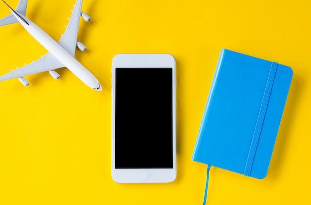 Smartphone à écran vide, avion décoratif et ordinateur portable, modèle de présentation d'application.