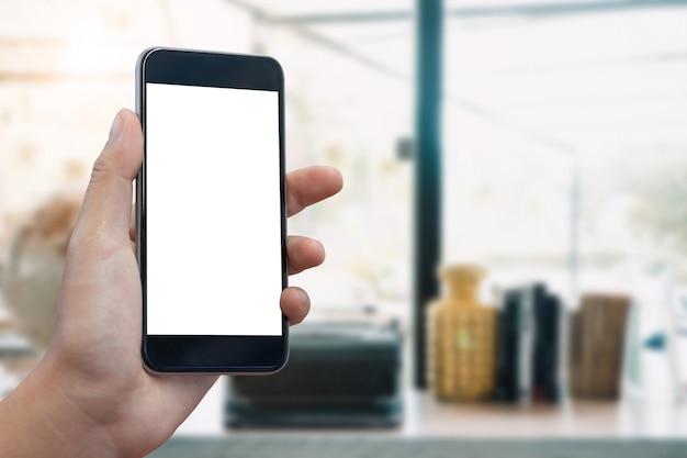 Smartphone écran vide chez la femme les mains sur l'arrière-plan flou au café.