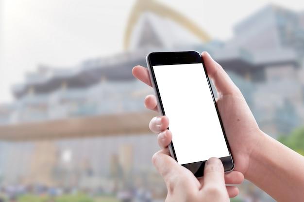 Smartphone écran vide chez la femme les mains sur l'arrière-plan flou au centre commercial.