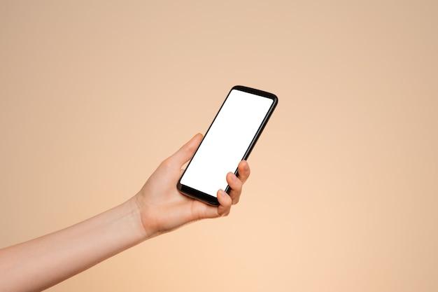 Smartphone avec un écran vide dans la main d'une femme sur fond orange.