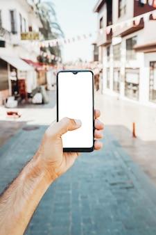 Smartphone écran vide à la main sur le fond d'une rue touristique dans les applications de la ville et t...