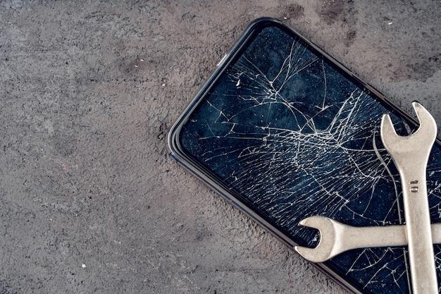 Smartphone écrasé avec des outils de réparation sur fond gris