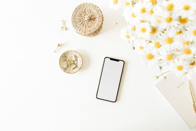 Smartphone avec espace copie maquette vierge sur table avec bouquet de fleurs de marguerite de camomille sur une surface blanche