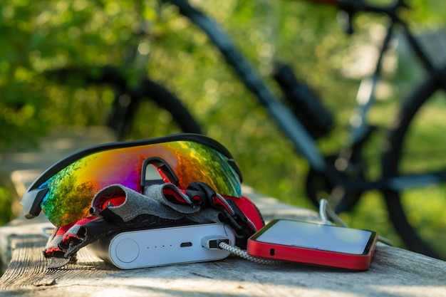 Le smartphone est chargé à l'aide d'un chargeur portable. banque d'alimentation dans la forêt sur le fond d'un vélo.