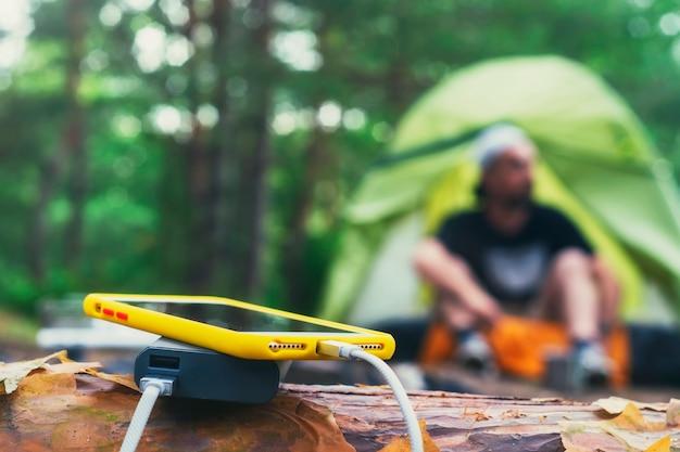 Le smartphone est chargé à l'aide d'un chargeur portable. power bank charge le téléphone à l'extérieur avec un sac à dos dans le contexte d'une tente et d'un touriste.