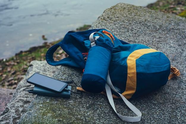 Le smartphone est chargé à l'aide d'un chargeur portable. power bank charge le téléphone à l'extérieur avec un sac à dos pour le tourisme dans la nature.