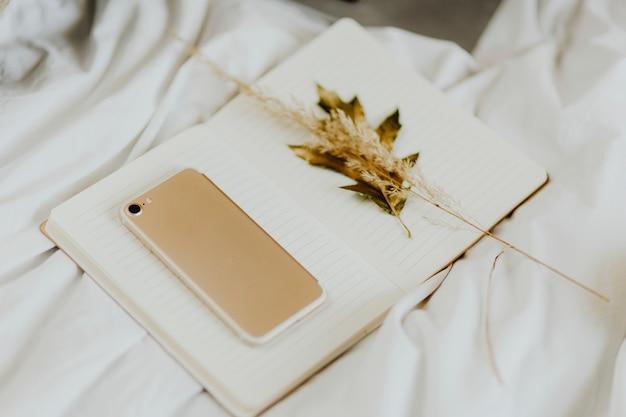 Smartphone et fleurs séchées sur un cahier vierge