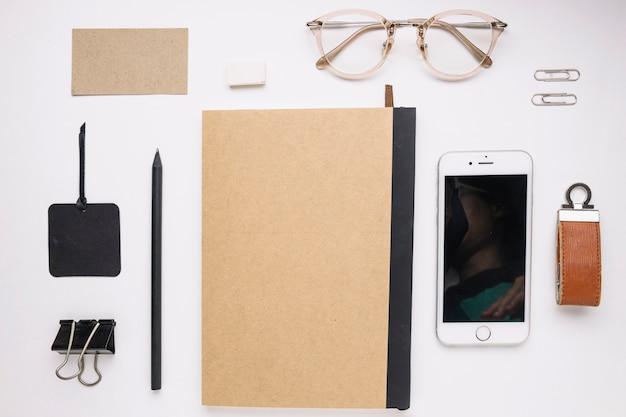 Smartphone et lunettes près de bloc-notes fermé