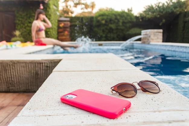 Smartphone et lunettes de soleil au bord d'une piscine, avec une fille qui éclabousse de l'eau en arrière-plan - concept d'été.
