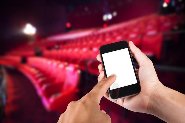 Smartphone à la main et écran blanc avec un fond flou de siège dans le cinéma.