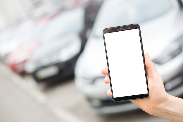 Smartphone à la main avec un écran blanc sur le fond des voitures en stationnement.