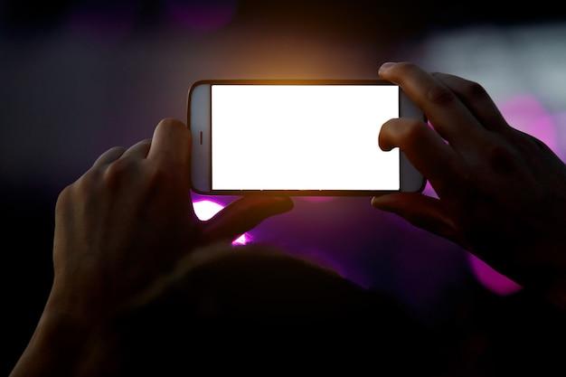 Un smartphone à la main enregistre un spectacle de musique en plein air.