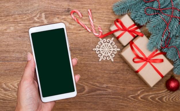 Smartphone en main féminine sur les décorations de noël. application pour faire des achats en ligne
