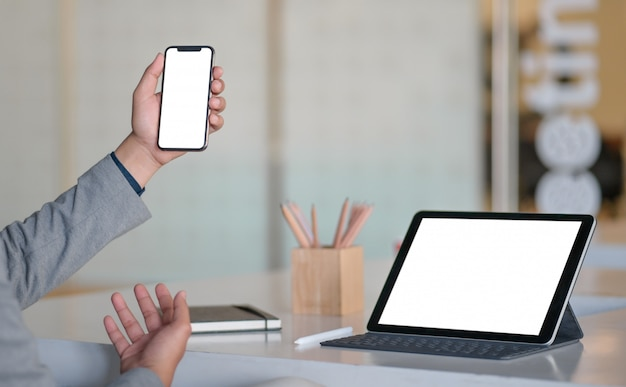 Smartphone en main et place de l'écran vierge de la tablette moderne sur le bureau.