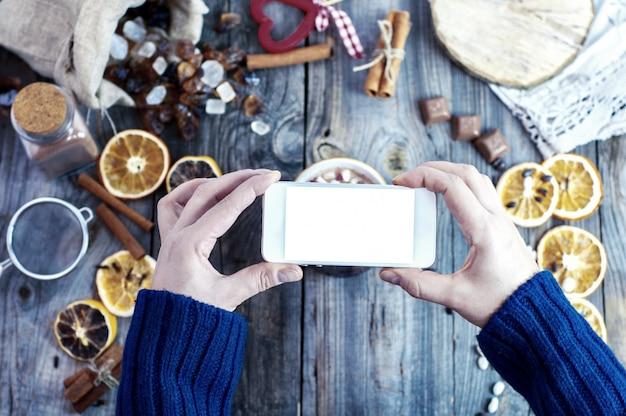 Smartphone en mains féminines, processus de photographie de la nourriture
