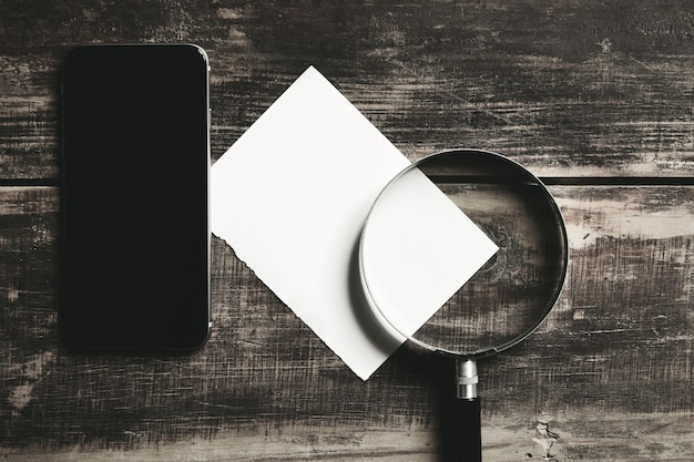 Smartphone mobile, loupe et feuille de papier blanc isolé sur table en bois de ferme noire concept de jeu de détective mystérieux.