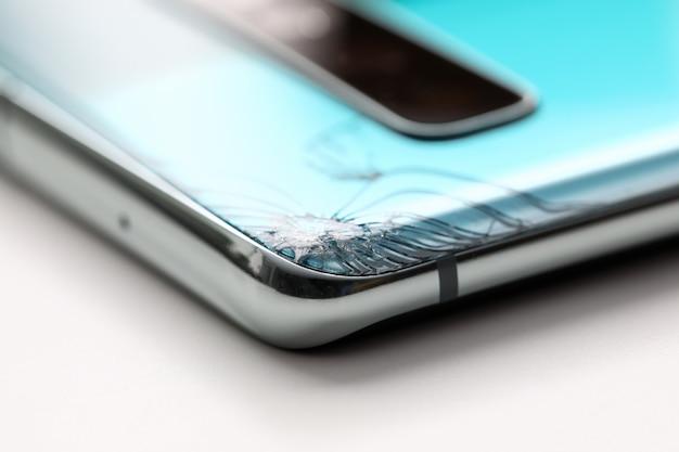 Smartphone moderne allongé à table avec fissure dans le coin