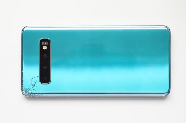 Smartphone moderne allongé à table avec fissure en gros plan d'angle