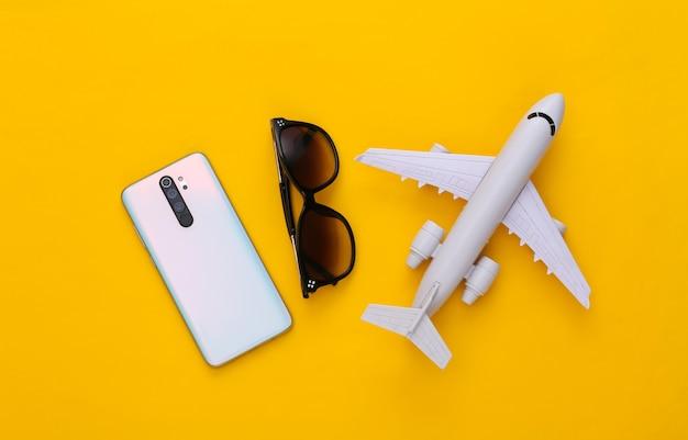 Smartphone moderne, avion et lunettes de soleil sur jaune. concept de voyage