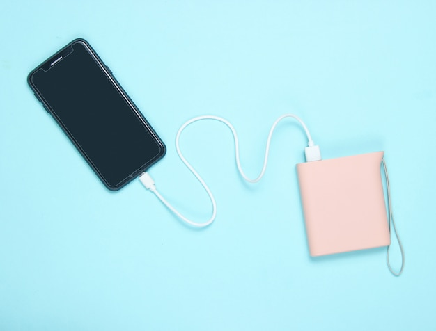 Smartphone moderne en charge avec banque d'alimentation sur bleu. vue de dessus