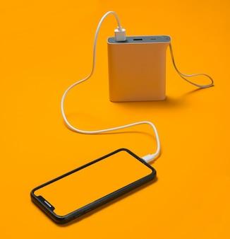 Smartphone moderne en charge avec power bank sur jaune.