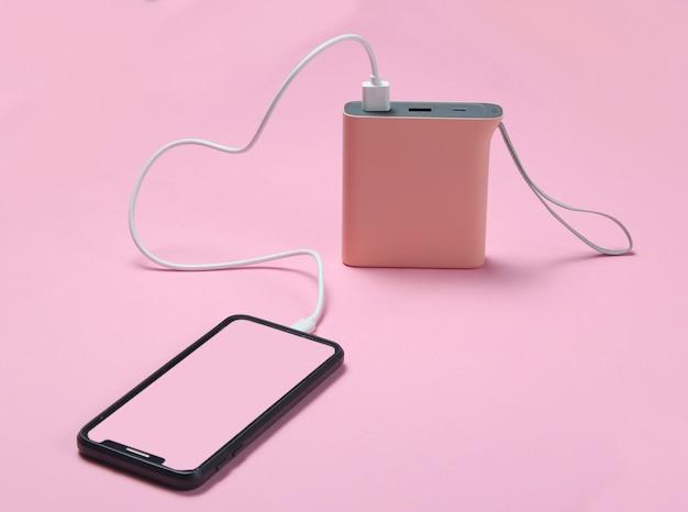Smartphone moderne en charge avec power bank sur rose pastel.