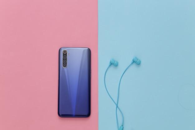 Smartphone moderne avec des écouteurs bleus sur pastel bleu rose