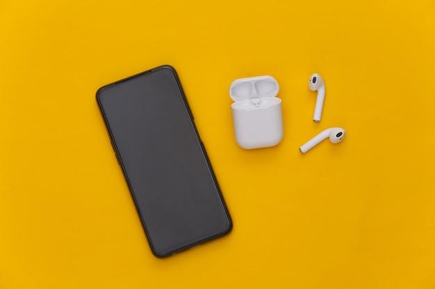 Smartphone moderne et écouteurs sans fil avec étui de chargement sur fond jaune.