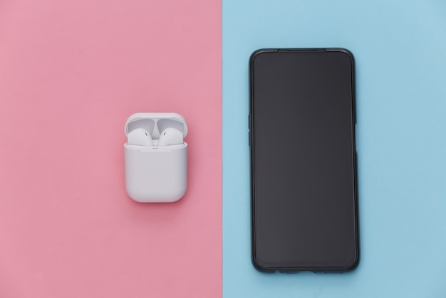 Smartphone moderne et écouteurs sans fil avec étui de chargement sur fond pastel bleu rose.
