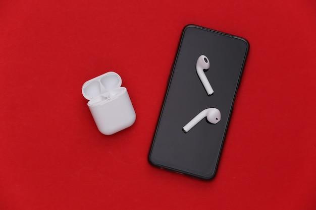 Smartphone moderne et écouteurs sans fil avec étui de chargement sur fond rouge.