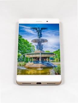 Smartphone moderne avec photo de la fontaine bethesda à new york, usa. concept pour la photographie de smartphone de voyage. toutes les images de cette composition sont réalisées par mes soins et disponibles séparément sur mon portfolio