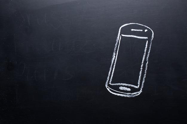 Smartphone noir et blanc sur tableau noir