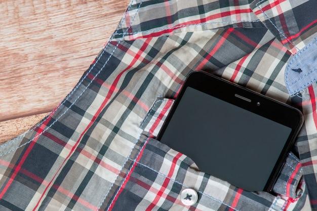 Smartphone noir sortant d'une poche de chemise sans manches