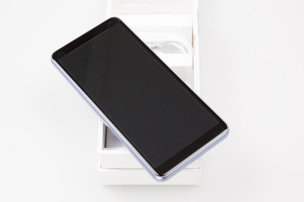 Smartphone nouveau et moderne dans une boîte blanche isolé sur blanc