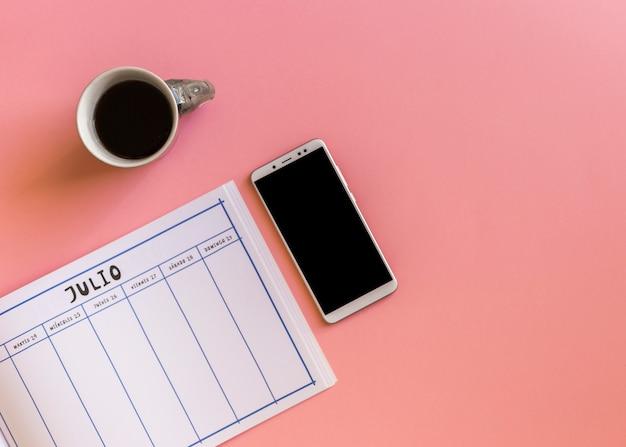 Smartphone avec ordinateur portable et café sur la table