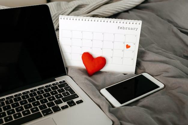 Smartphone, ordinateur portable et calendrier avec la date du 14 février.