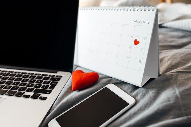 Smartphone, ordinateur portable et un calendrier avec la date de la saint-valentin.