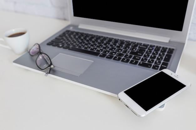 Smartphone sur l'ordinateur portable avec des lunettes et une tasse de café