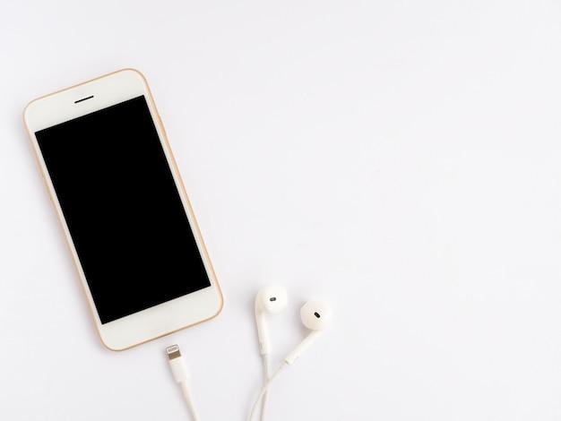 Smartphone, oreillettes et câble de charge sur blanc