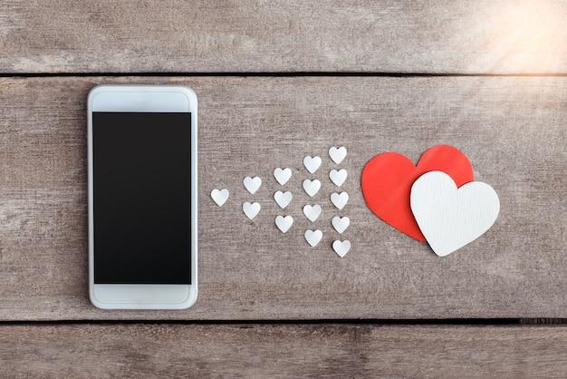 Smartphone et papier de coeurs sur fond en bois